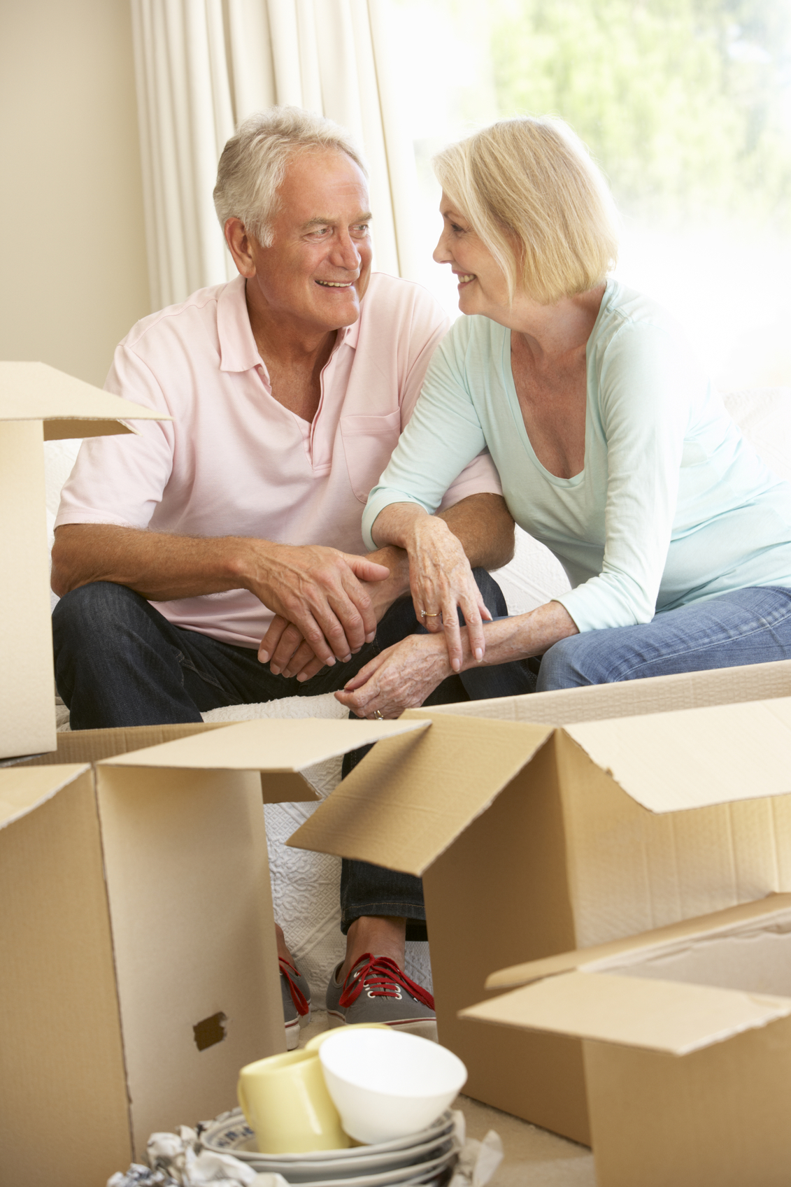 Senior Couple Moving Into New Home Surrounded By Packing Boxes And Smiling on Sofa